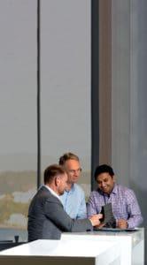Guy, Grant and Vishnu at standing desk looking at iPad