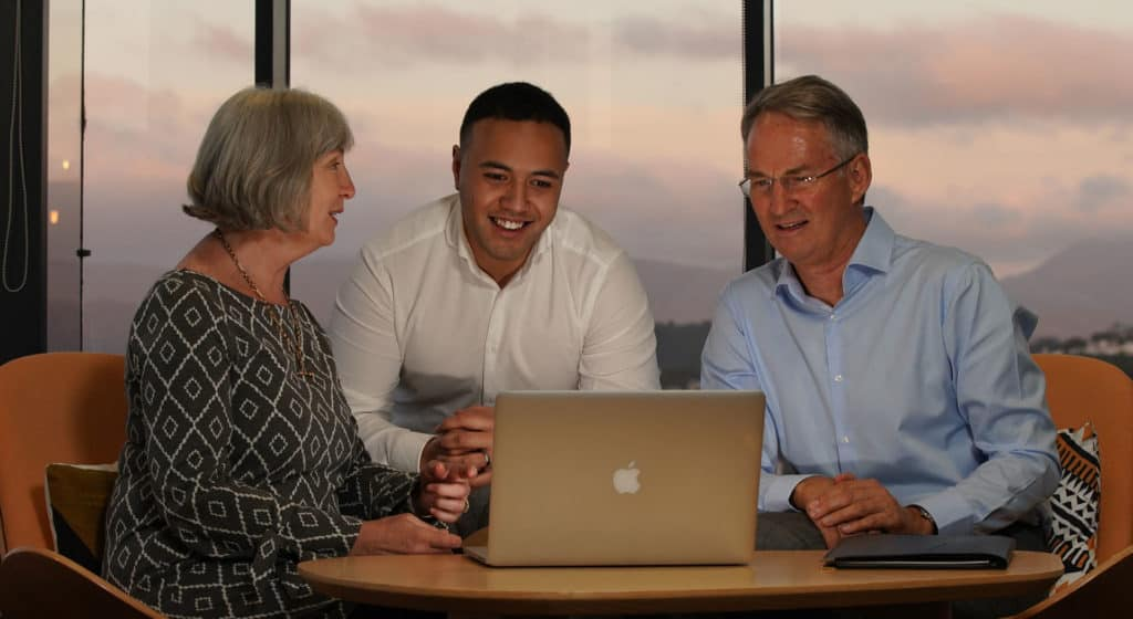 Raewyn, Fredwyn and Grant seated in front of a laptop reviewing a clients brief